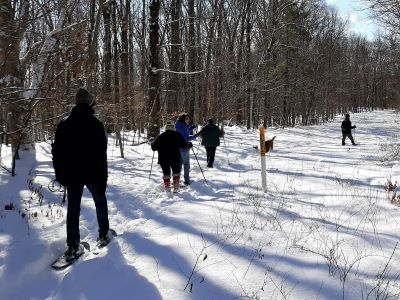 Photograph of a small group of hikers walking on a snow-covered path in the woods of Speer Preserve with snow shoes.